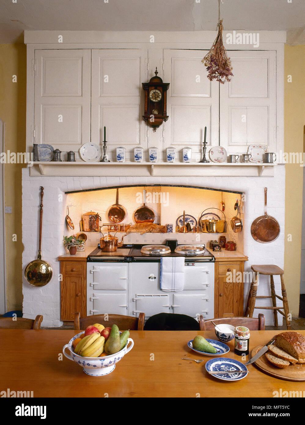 Un país rústico, cocina con mesa de granja, blanco Aga en el receso ...