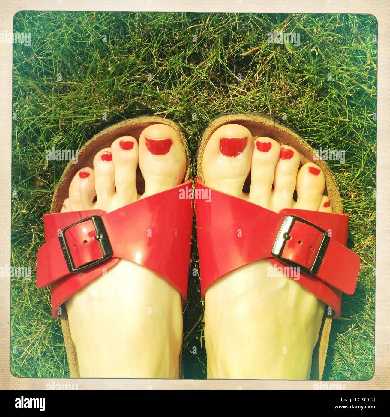 Dedos del pie pintados en sandalias sobre el césped Imagen De Stock
