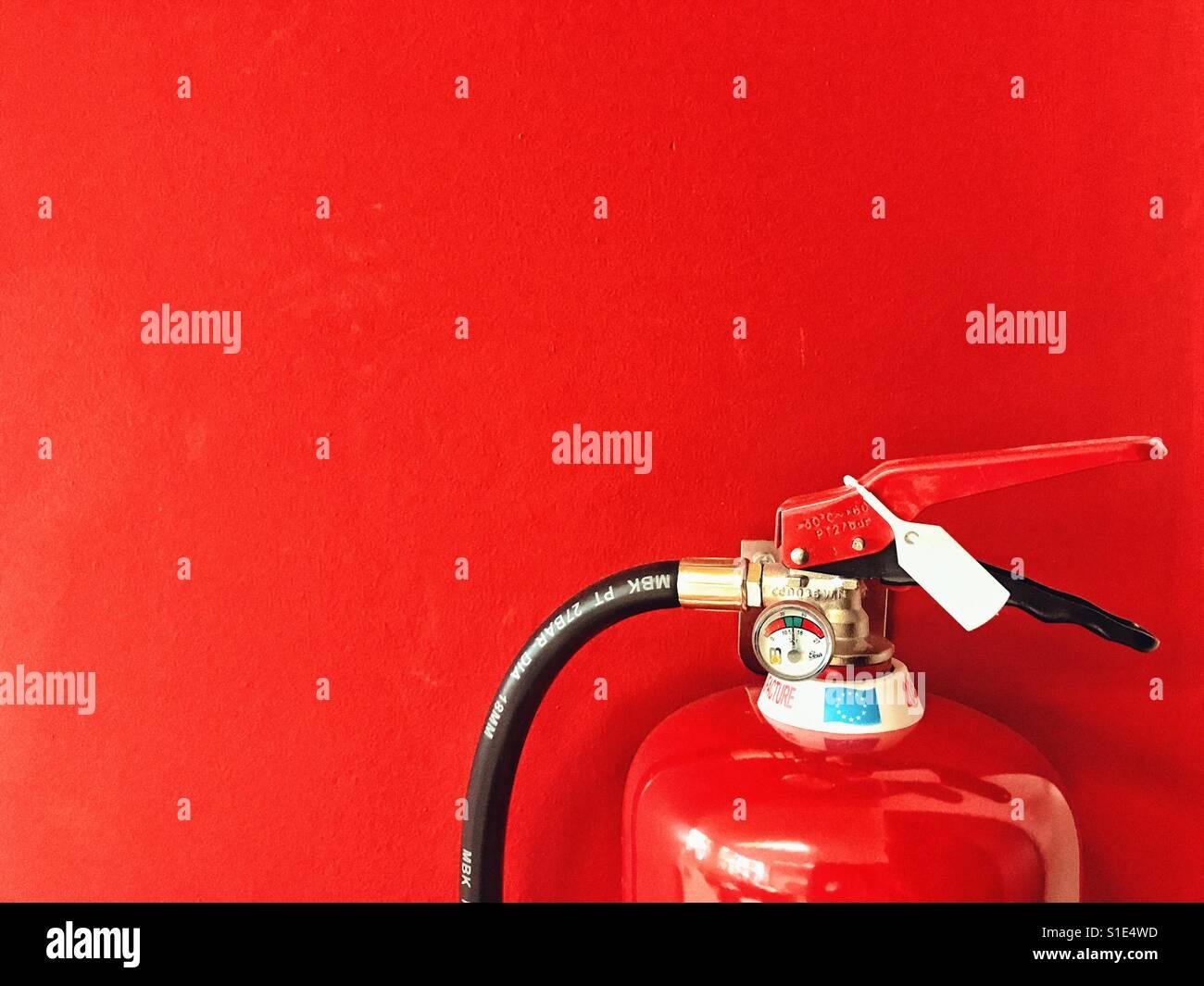 Detalle de extintor contra un fondo rojo. Imagen De Stock