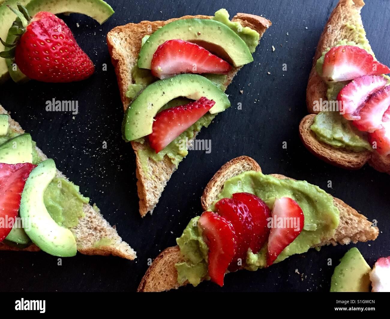 Las tostadas de aguacate con fresas Imagen De Stock