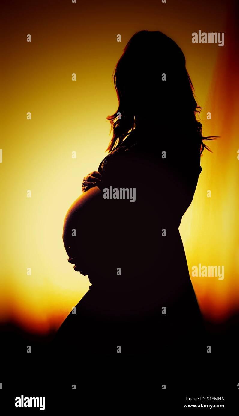 Silueta de una mujer embarazada en la puesta de sol Imagen De Stock