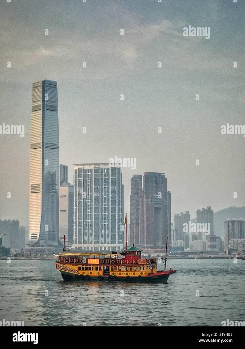 """El """"ala"""" de viaje, un double decker junco chino, llevando a los turistas en un crucero por el Puerto Victoria en penumbra, en frente de la CPI, el rascacielos más alto de Hong Kong, en el oeste de Kowloon Imagen De Stock"""