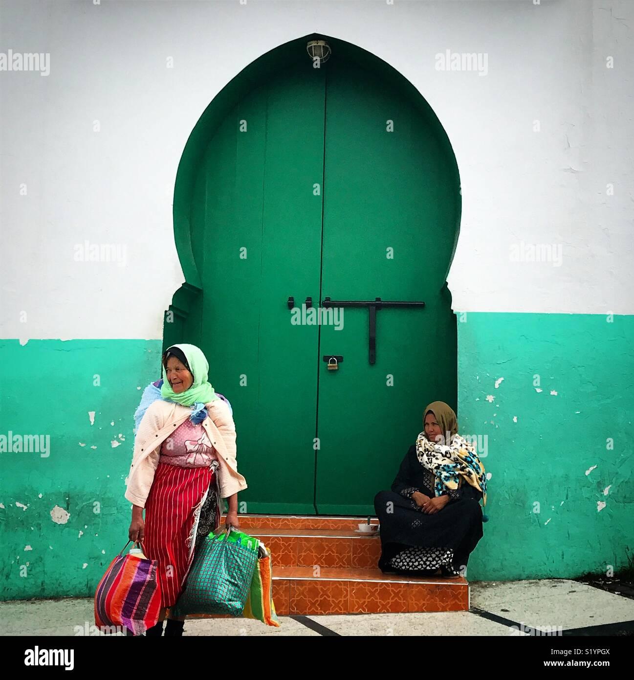 Las mujeres marroquíes sentarse delante de una puerta verde en Tánger, Marruecos, África Imagen De Stock
