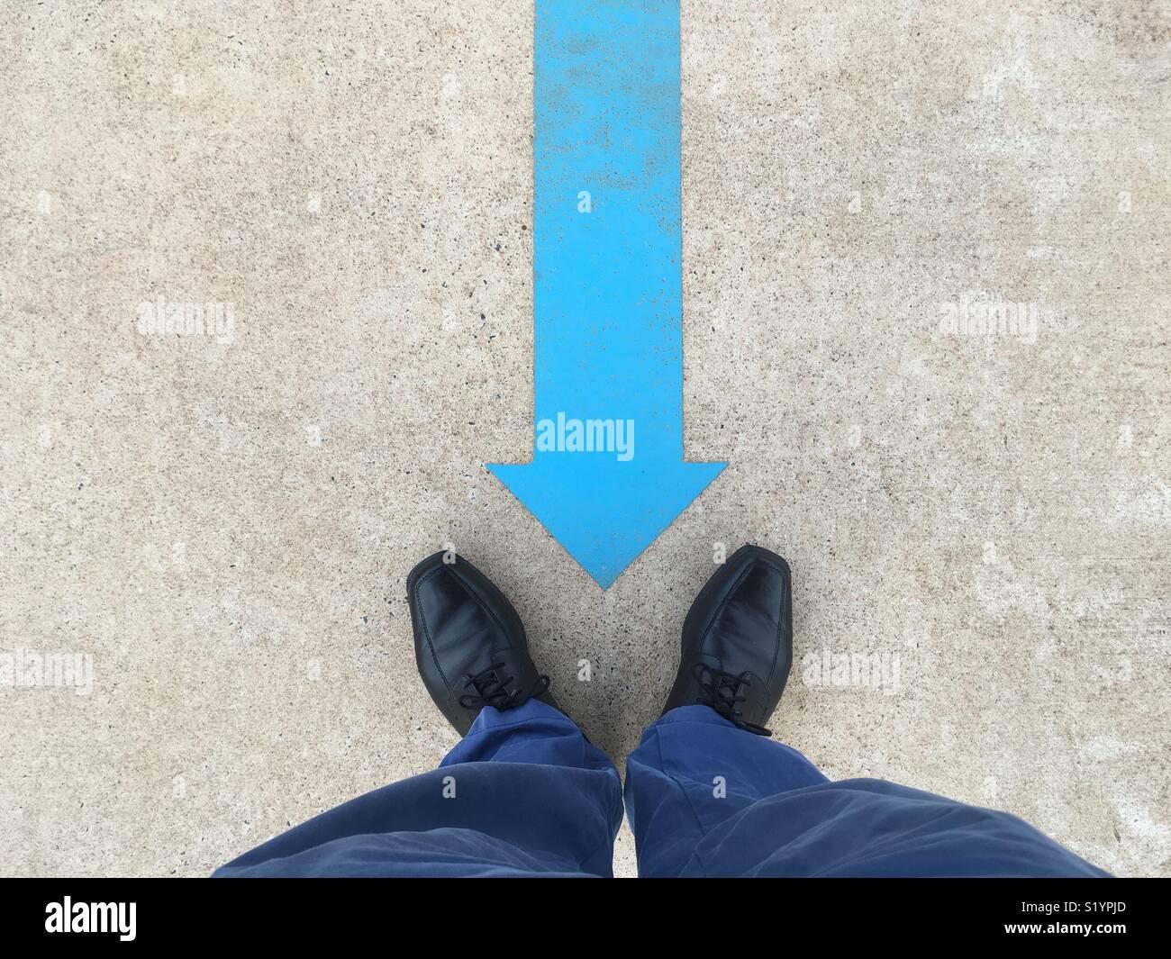 Una flecha azul pintada en el suelo apuntando a un hombre negro zapatos y pantalones azules. Imagen De Stock