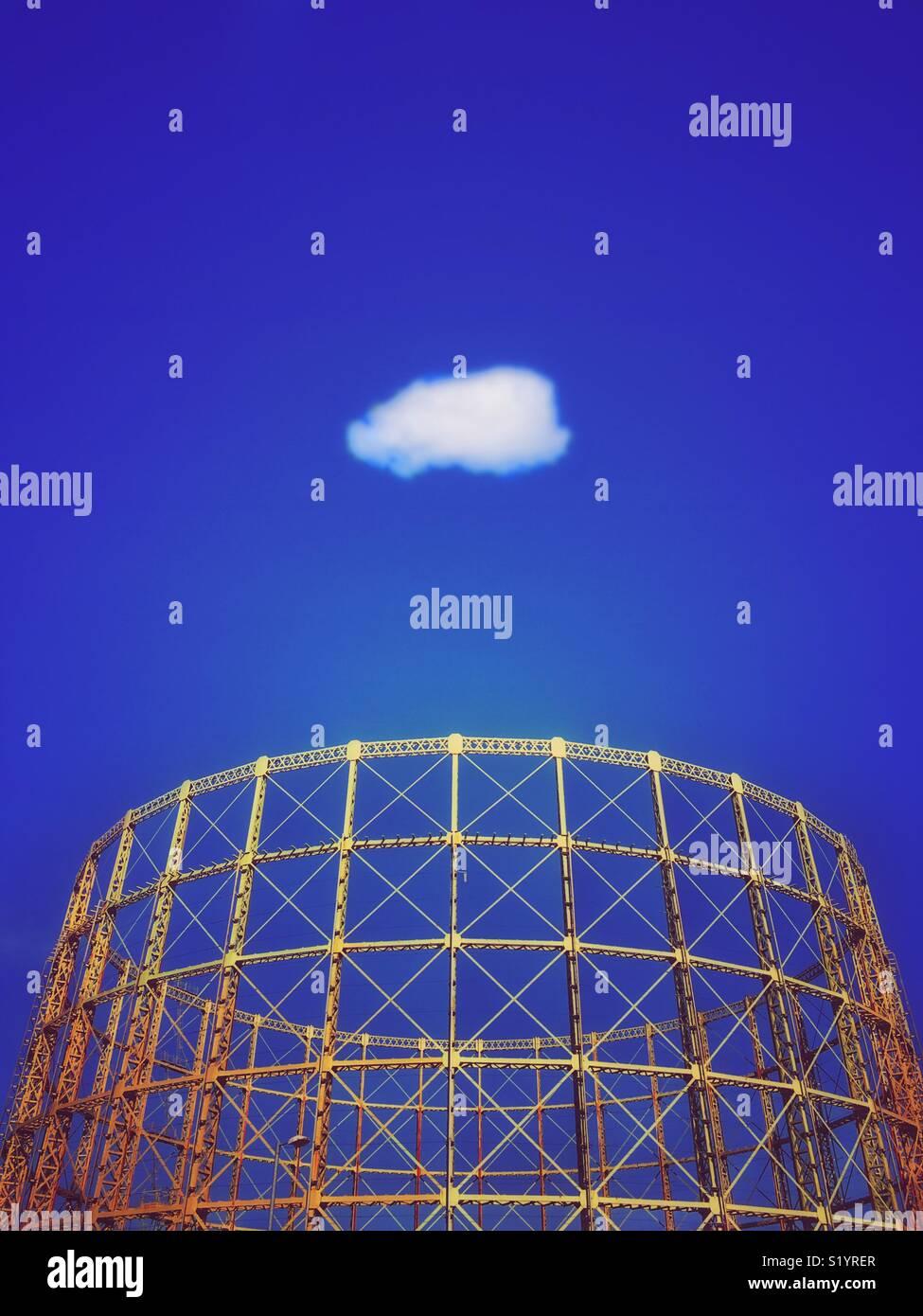 Gasómetro estructura contra un vívido cielo azul con nubes blancas solitario Imagen De Stock