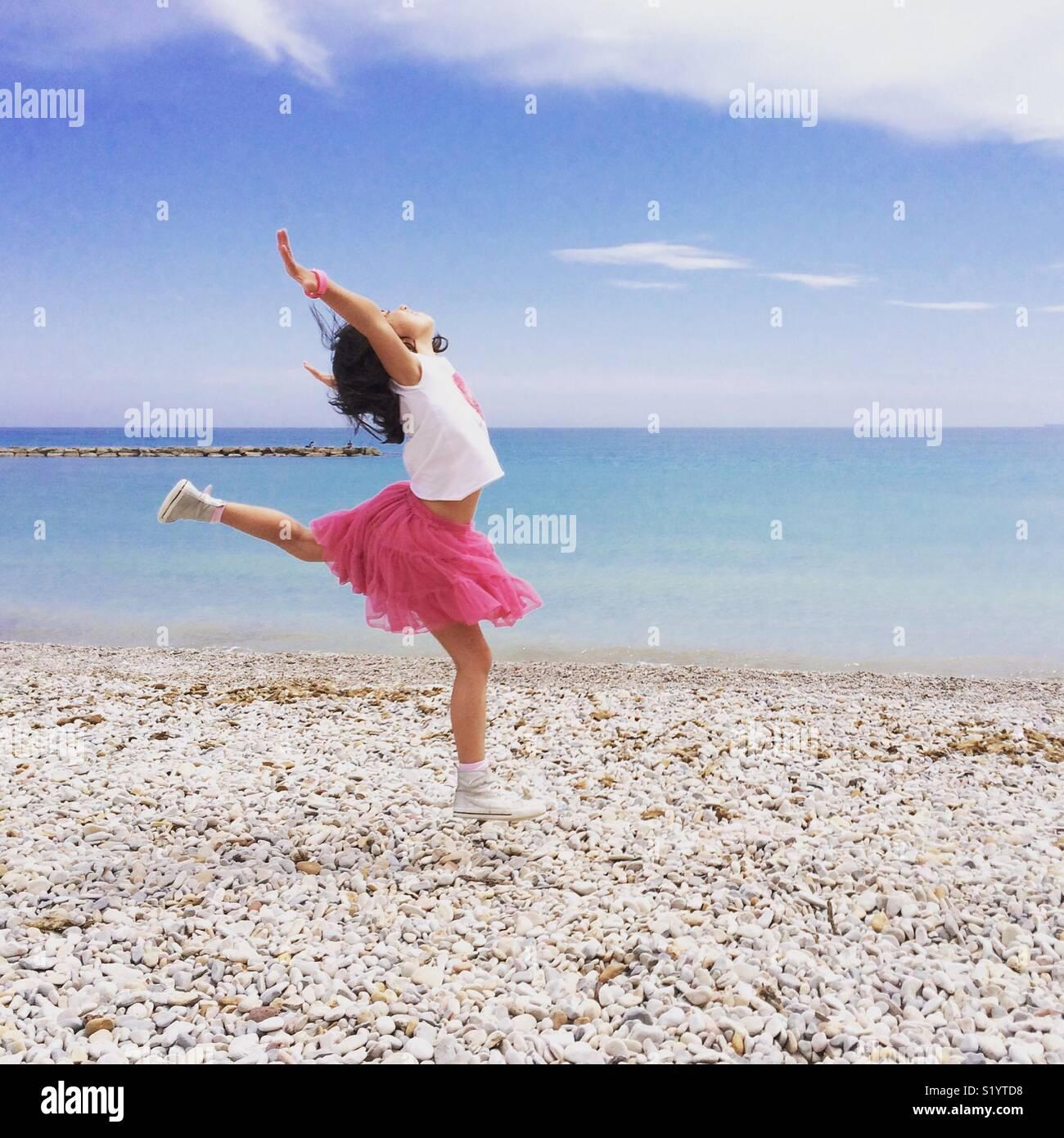 Chica en rosa falda de baile por la orilla del mar Mediterráneo. Imagen De Stock