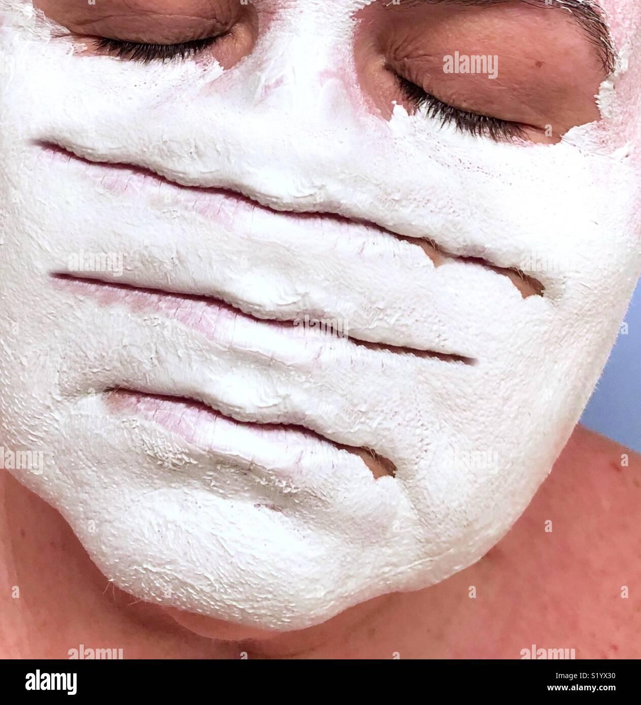 Una obra conceptual abstracto de una mujer con los ojos cerrados llevaba una máscara de barro de arcilla blanca con tres conjuntos de labios Imagen De Stock