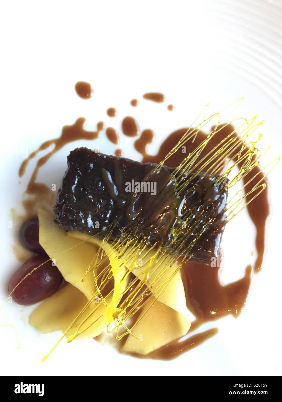 Bellamente presentado postre de Pudding de toffee con fruta y decoración de azúcar spin Imagen De Stock