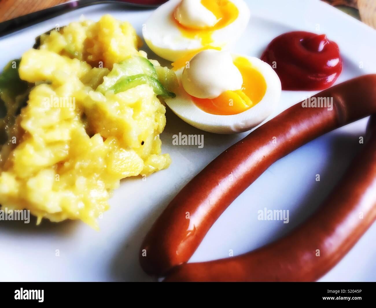 Un par de Viena, salchichas, huevos, mayonesa, ensalada de papas y salsa de tomate sobre una placa blanca. Imagen De Stock