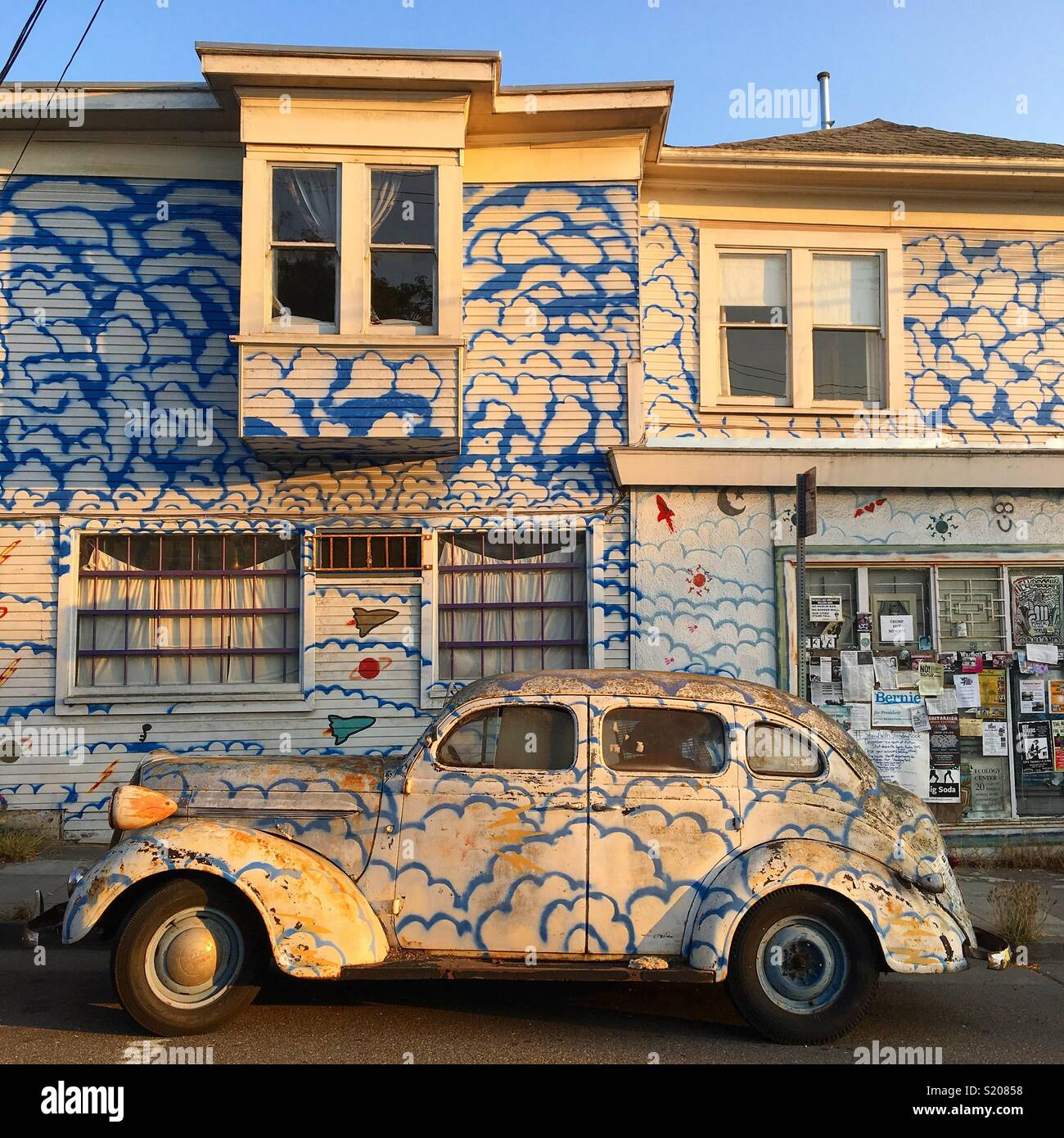 Un coche aparcado delante de una casa con pintura coincidentes Imagen De Stock
