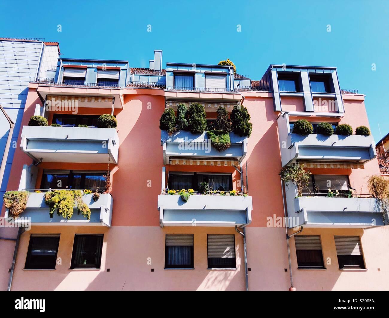El muelle de la ciudad. Casas coloreadas con ollas de verde en el balcón Imagen De Stock