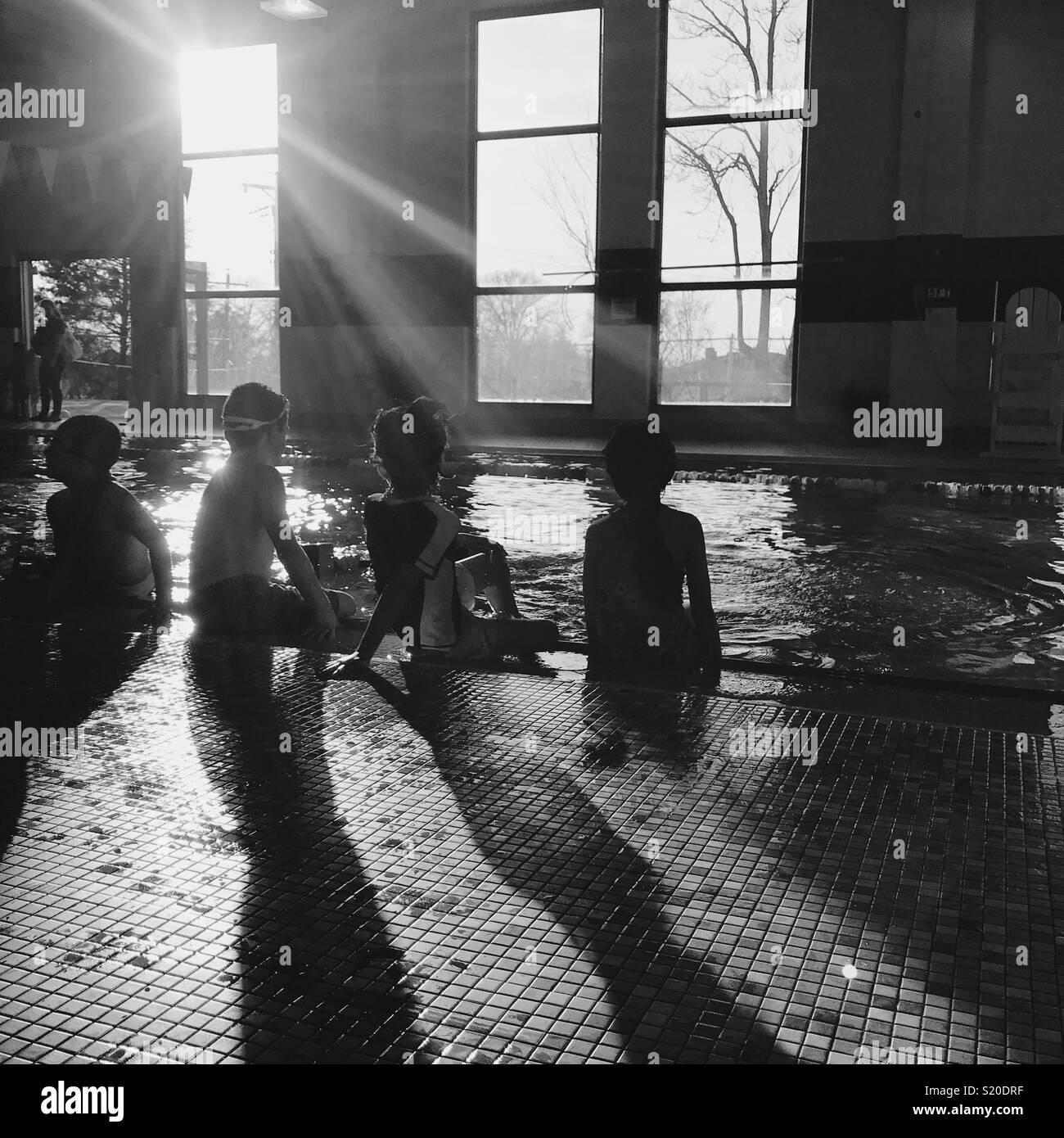4 niños en la piscina cubierta del invierno. Imagen De Stock
