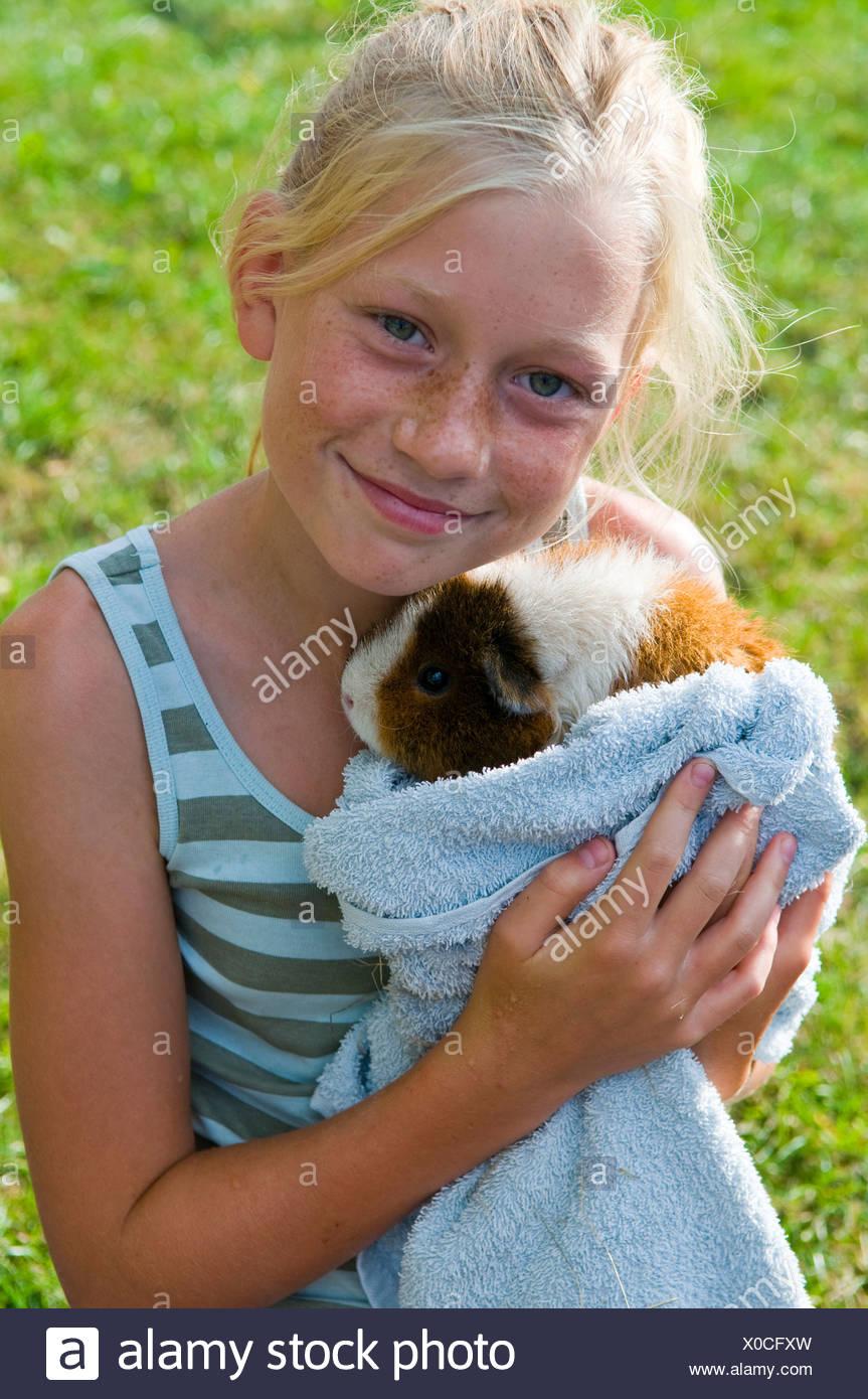 Close-up retrato de una linda niña con un conejillo de indias contra ...
