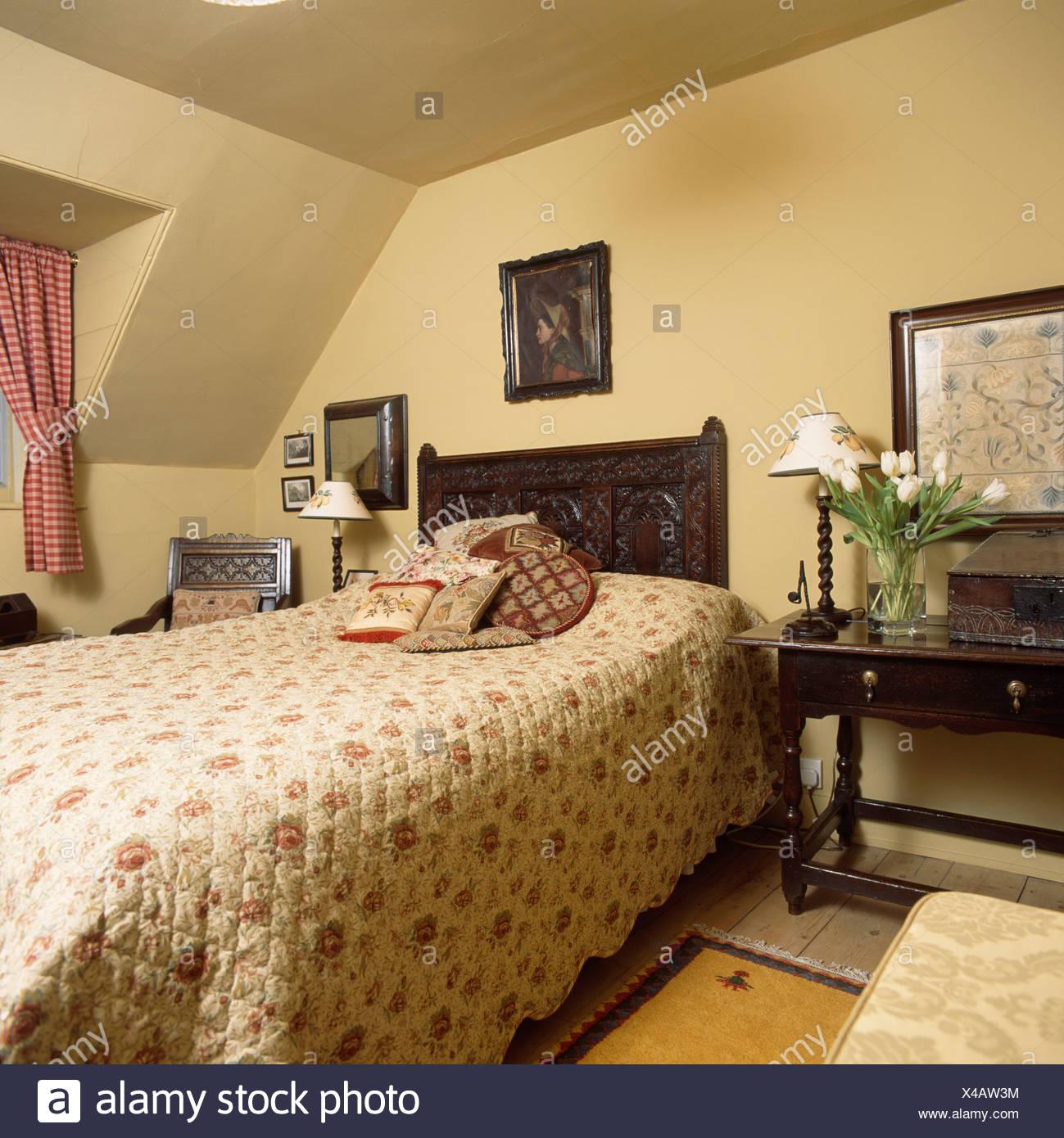 Rose telas colcha en la cama con cabecera de madera tallada en el ...
