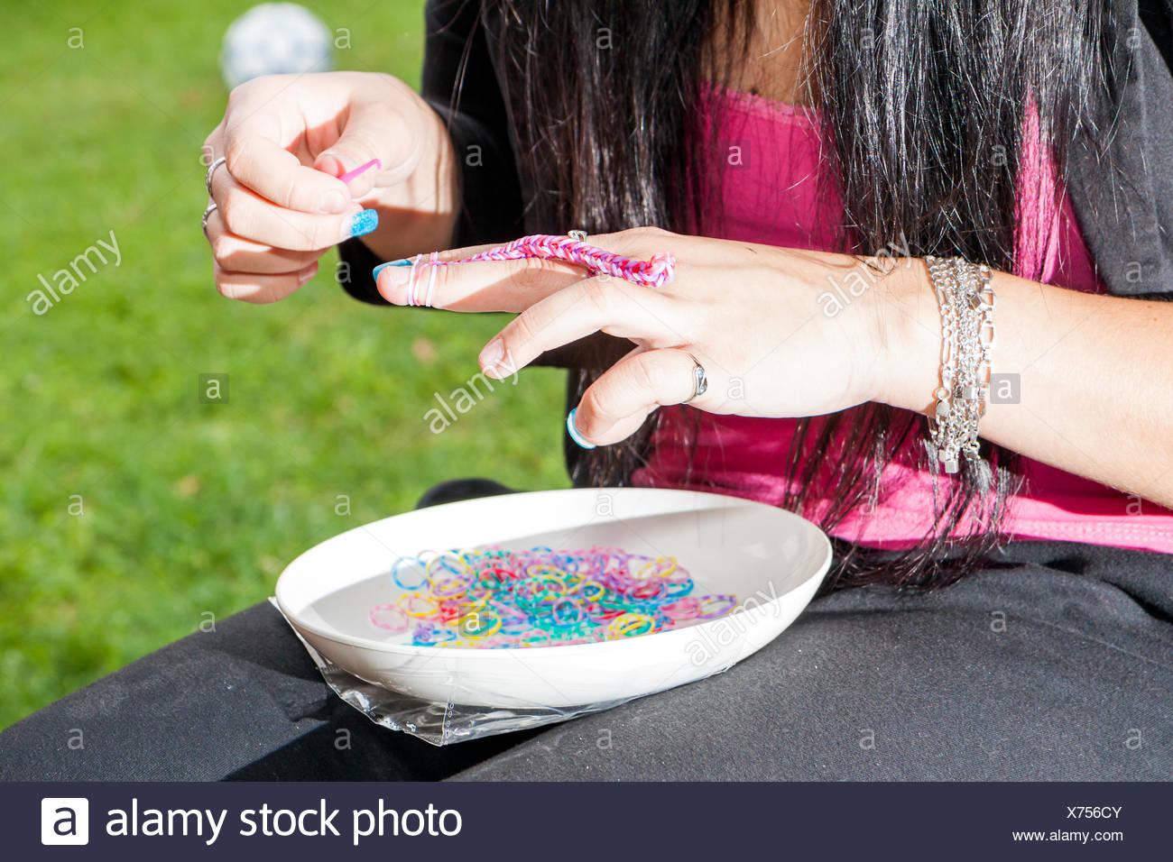 Chica con coloridas uñas haciendo un telar Pulsera de caucho con un ...