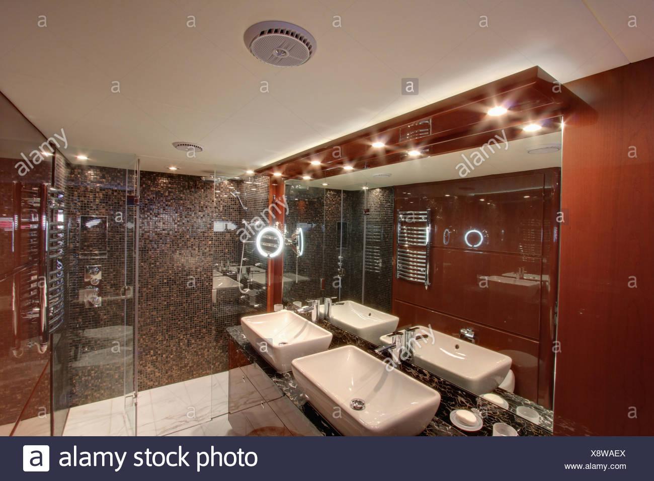 Iluminación descendente y espejo sobre lavabos dobles con cuarto de ...