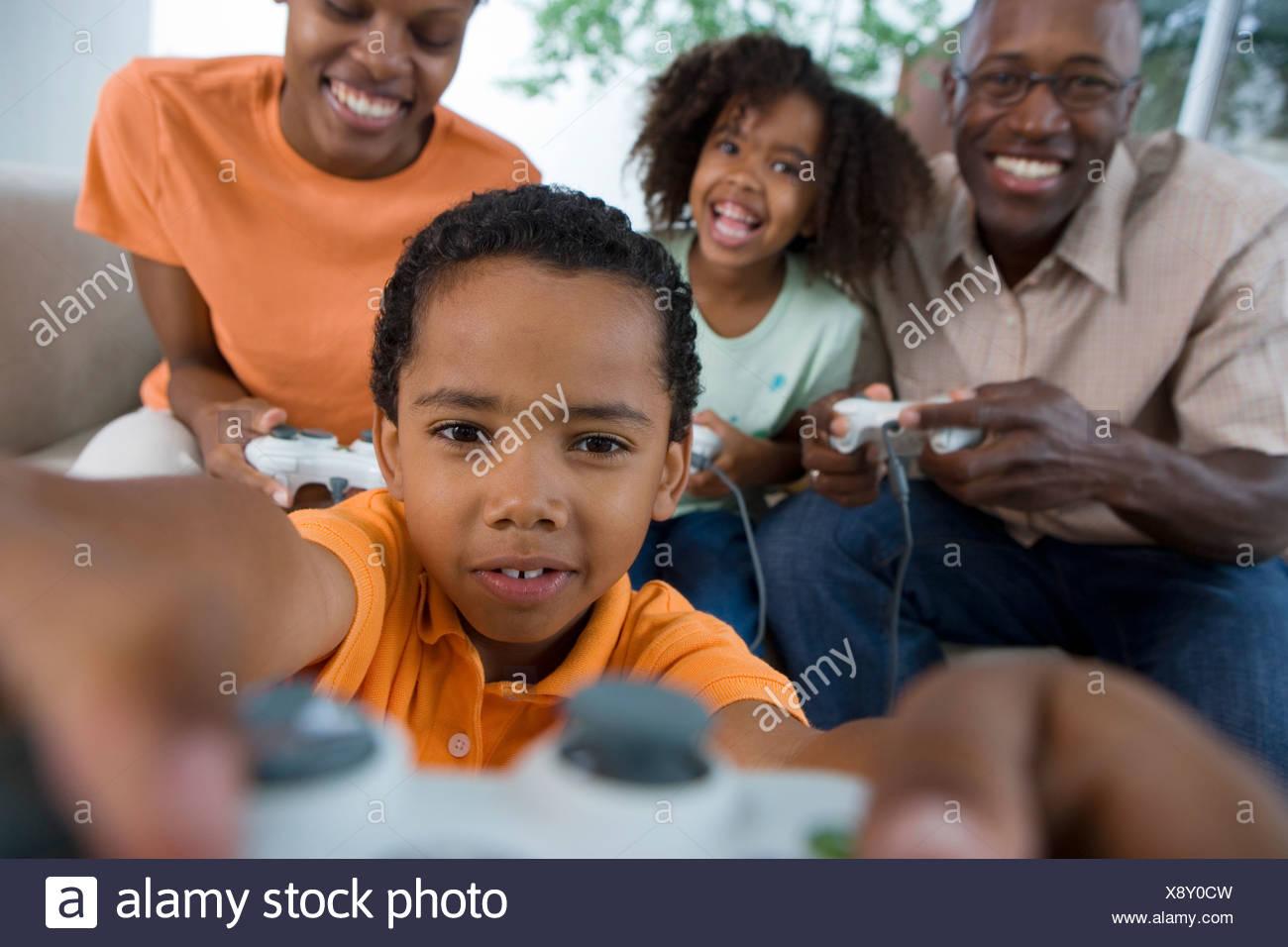 Familia Jugando Juegos De Video Consola En Sofa En Casa Sonriente