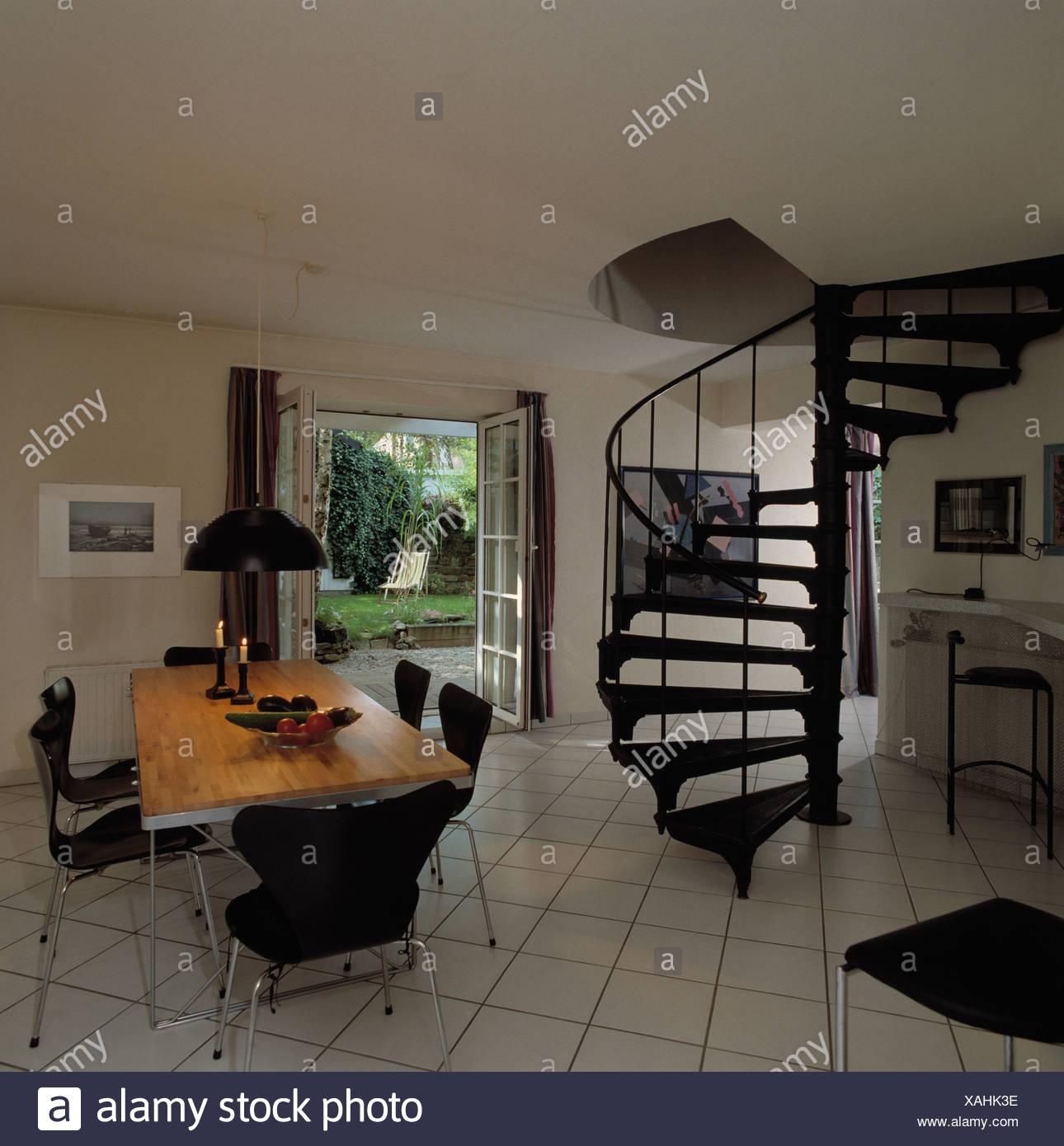 Escalera de caracol negro en blanco y moderno salón comedor con piso ...