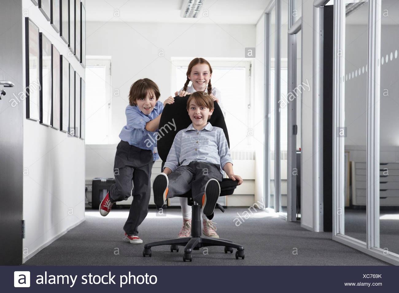 Tres niños jugando en el pasillo de oficina en silla de oficina Foto ...