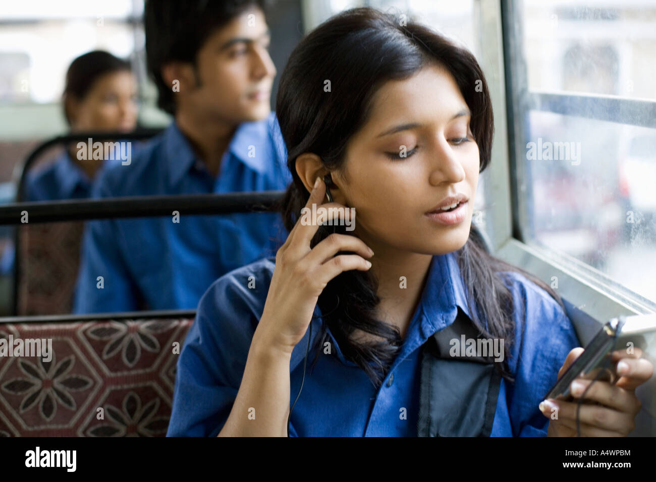 Female student listening to mp3 player sur le bus Photo Stock