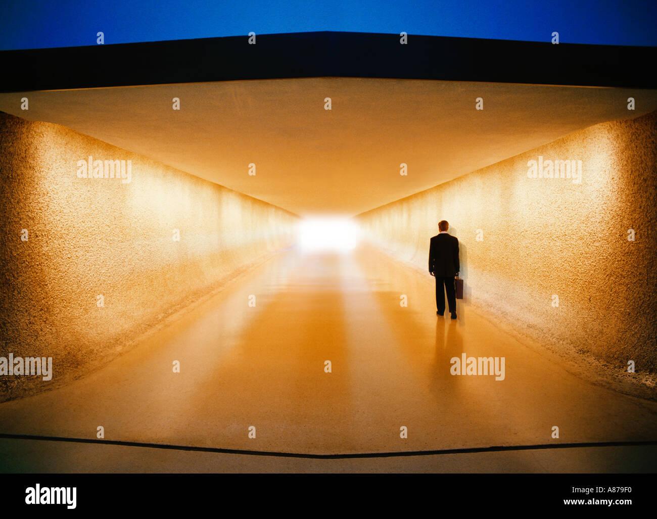 Businessman with briefcase walking down corridor vers la zone de récupération des bagages et du transport Photo Stock
