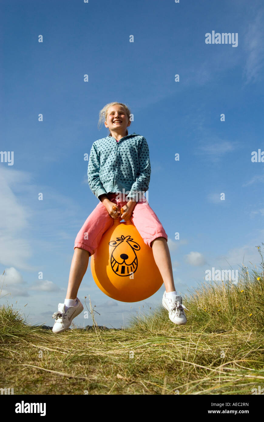 Jeune fille de rebondir sur un Space Hopper, England UK Photo Stock