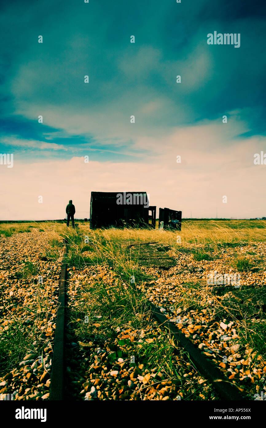 Homme debout à côté de shack sur une plage Photo Stock