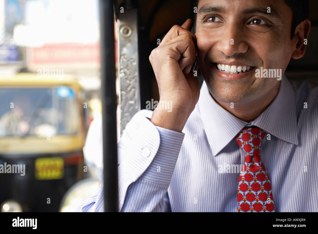 Business man using cell phone, smiling Photo Stock