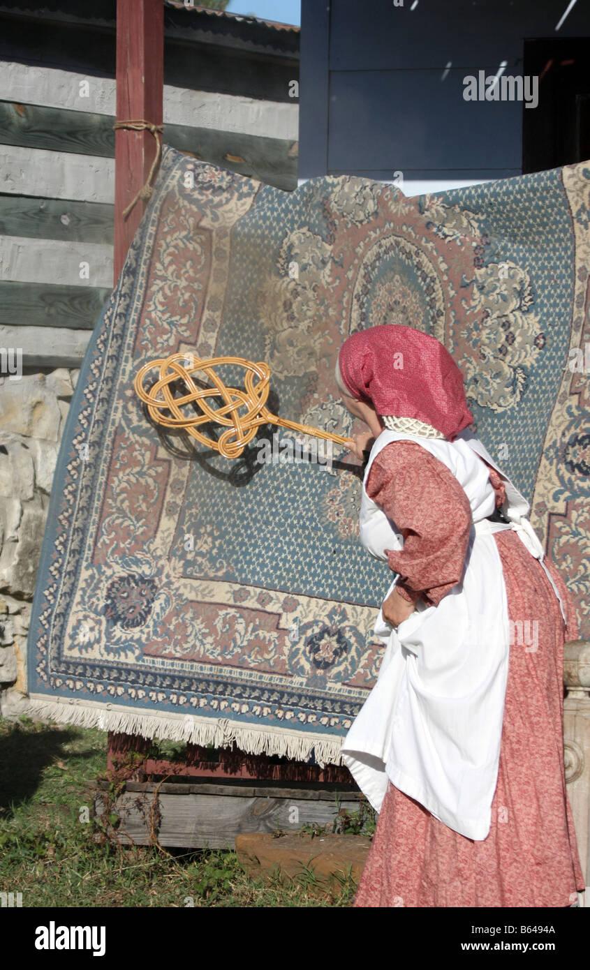 Devinette... - Page 2 Une-femme-plus-agee-de-battre-les-saletes-d-un-vieux-tapis-de-laine-sur-son-porche-homestead-b6494a