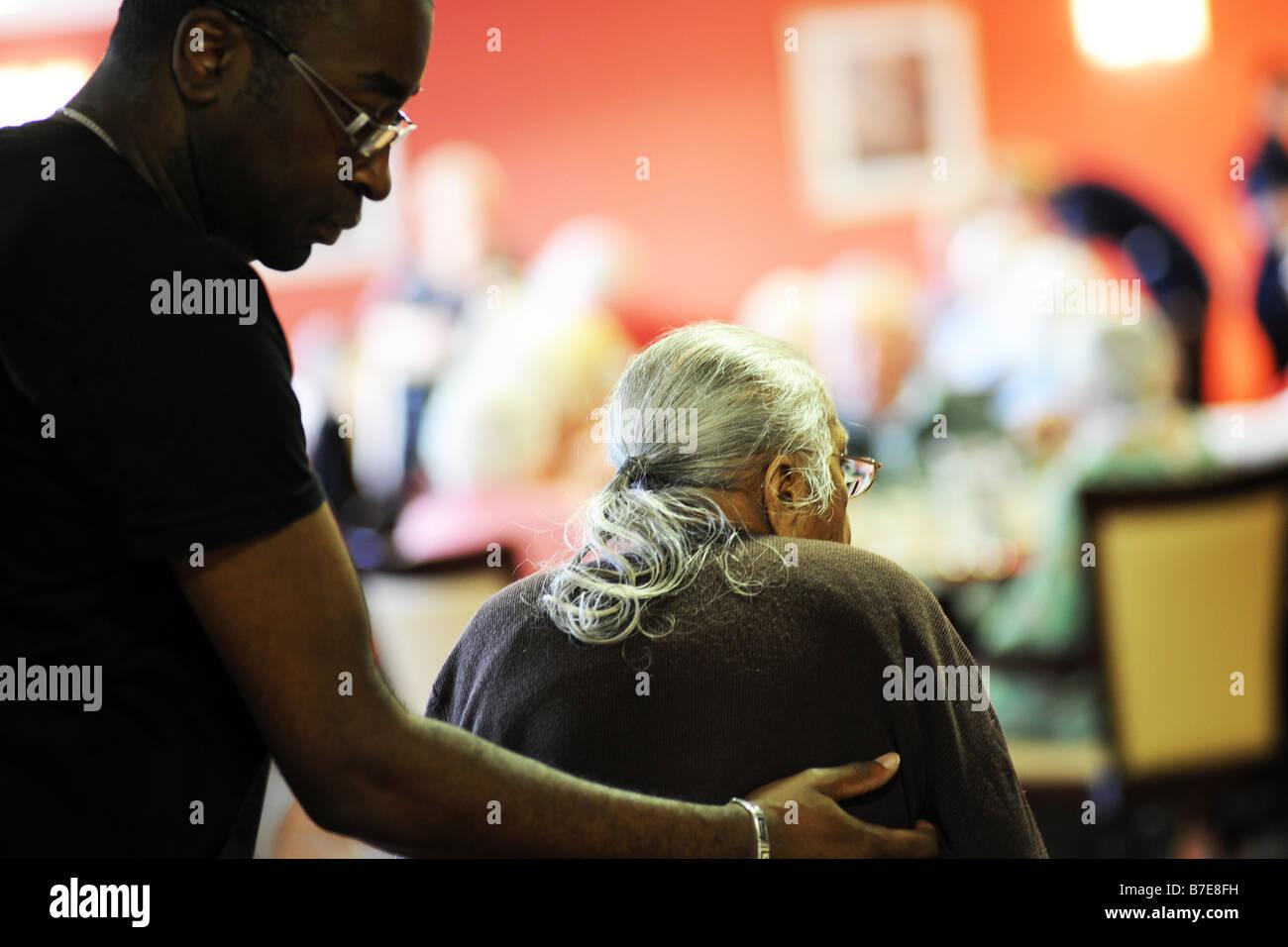Une vieille dame Sikh est aidé à sa chaise dans un contexte multiculturel de soin supplémentaire Photo Stock
