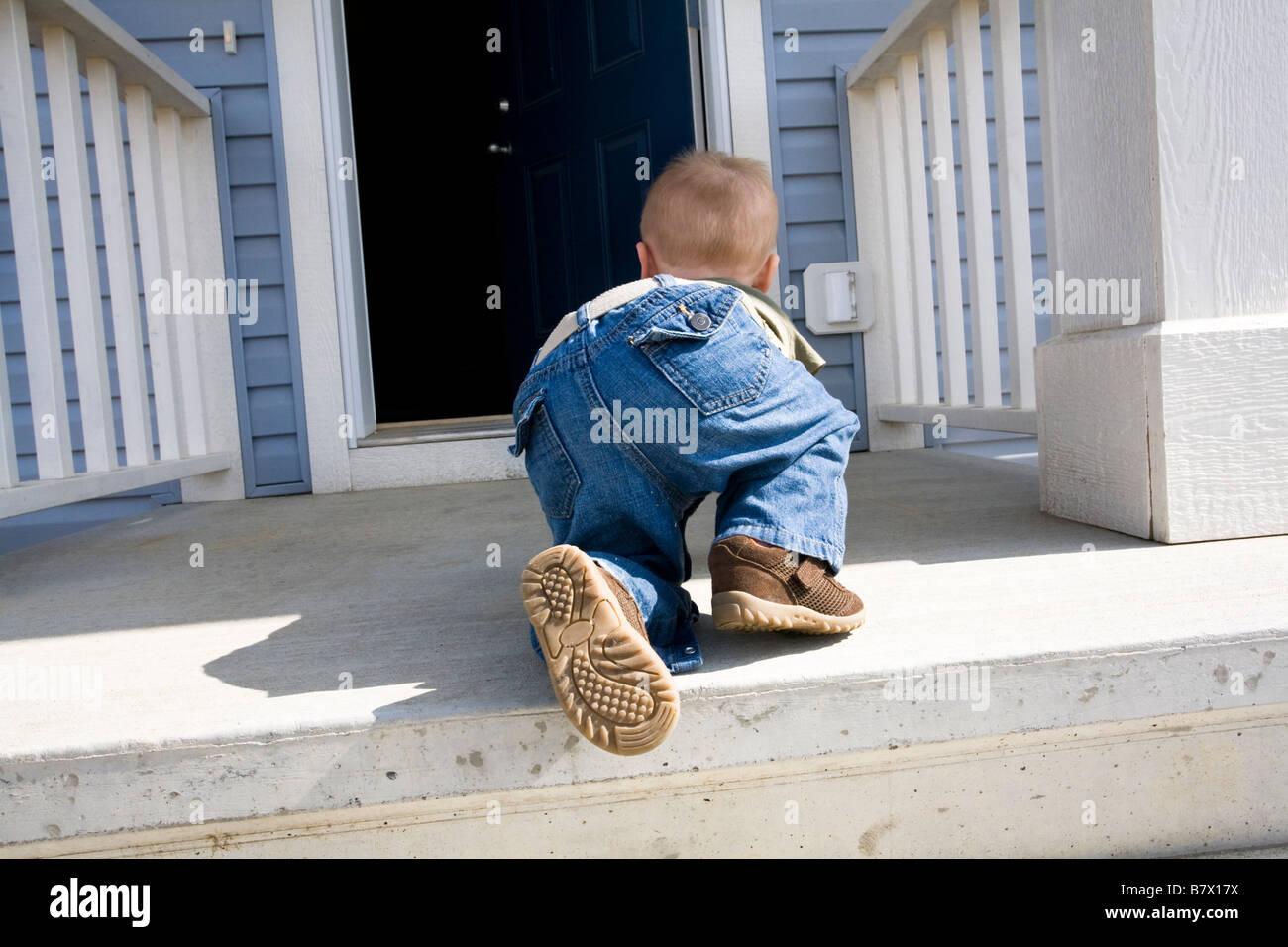 Enfant ramper vers la porte ouverte Photo Stock