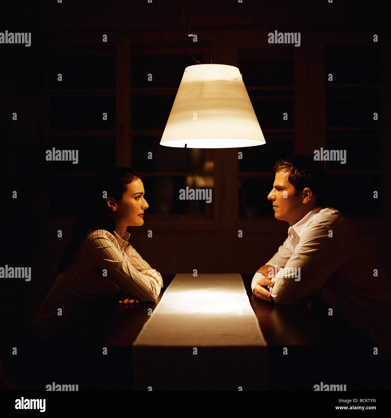 L'homme et la femme face à face à table Photo Stock