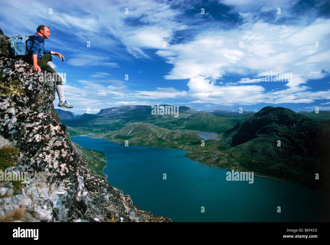 Assis au-dessus de Gjende randonneur (ou Gjendin) Lac dans les montagnes de Jotunheimen dans le parc national de Photo Stock