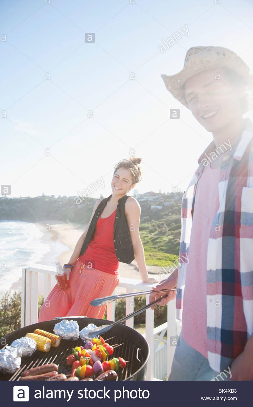L'homme et la femme ayant tendance barbecue avec ocean in background Photo Stock