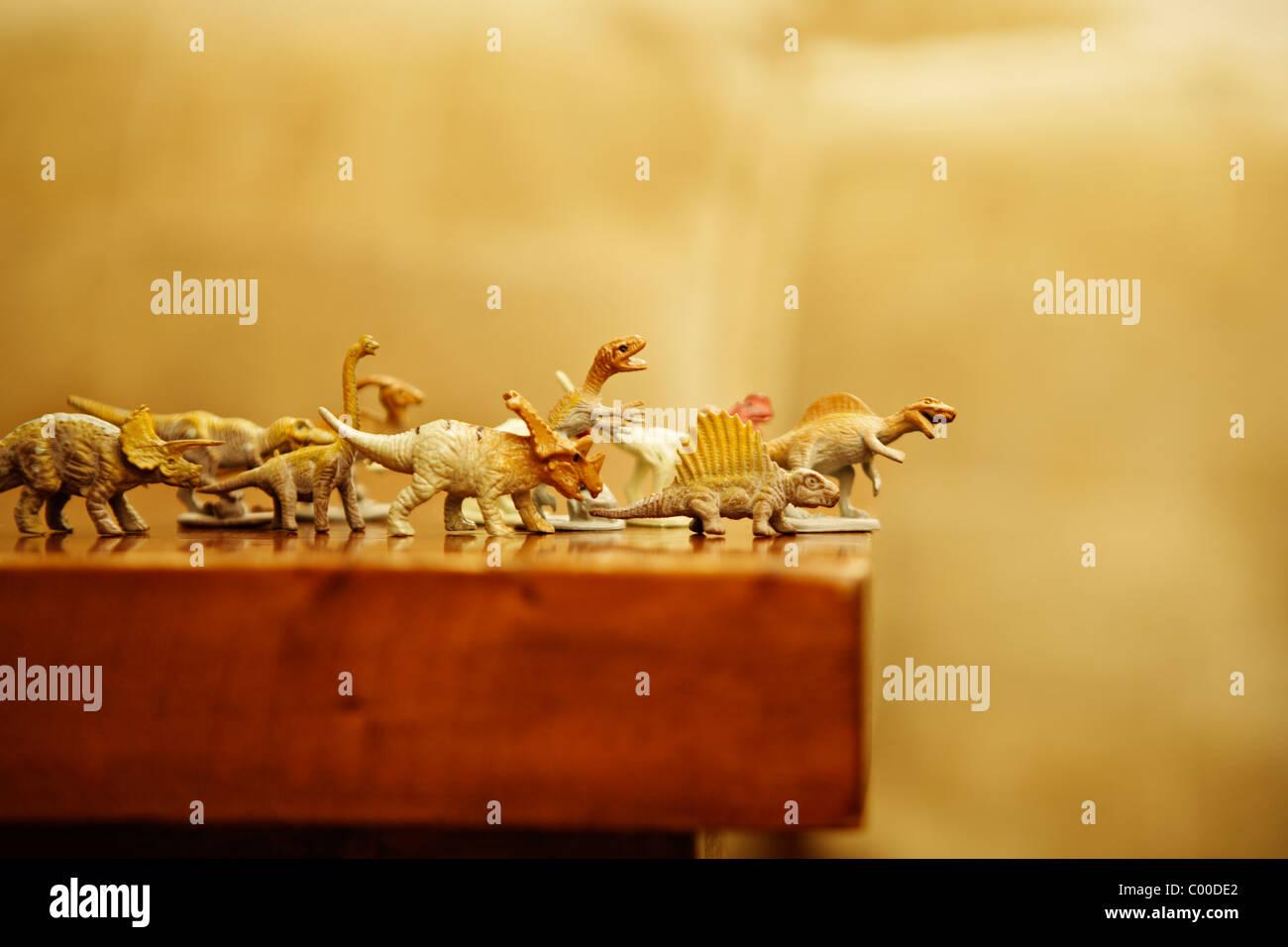 Dinosaures jouets se précipiter le rebord d'une table Photo Stock