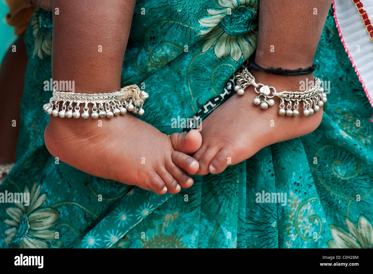 Les bébés indiens pieds nus contre les mères floral vert sari. L'Andhra Pradesh, Inde Photo Stock