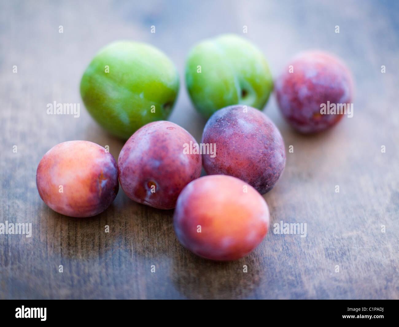 Les prunes vertes et violettes sur table en bois Photo Stock
