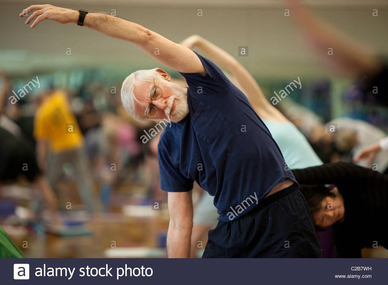 Un étirement latéral de poser dans un cours de yoga. Photo Stock