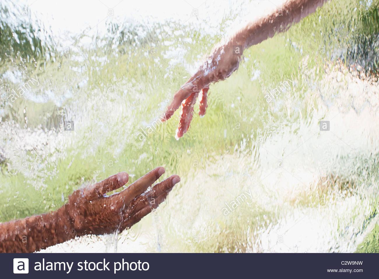 Deux mains tendues derrière une vitre Photo Stock