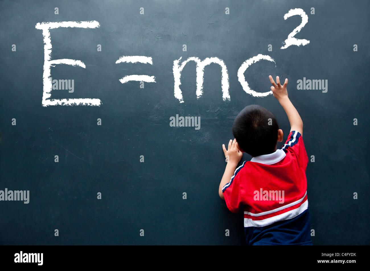 Boy drawing E=mc2 sur le mur Photo Stock