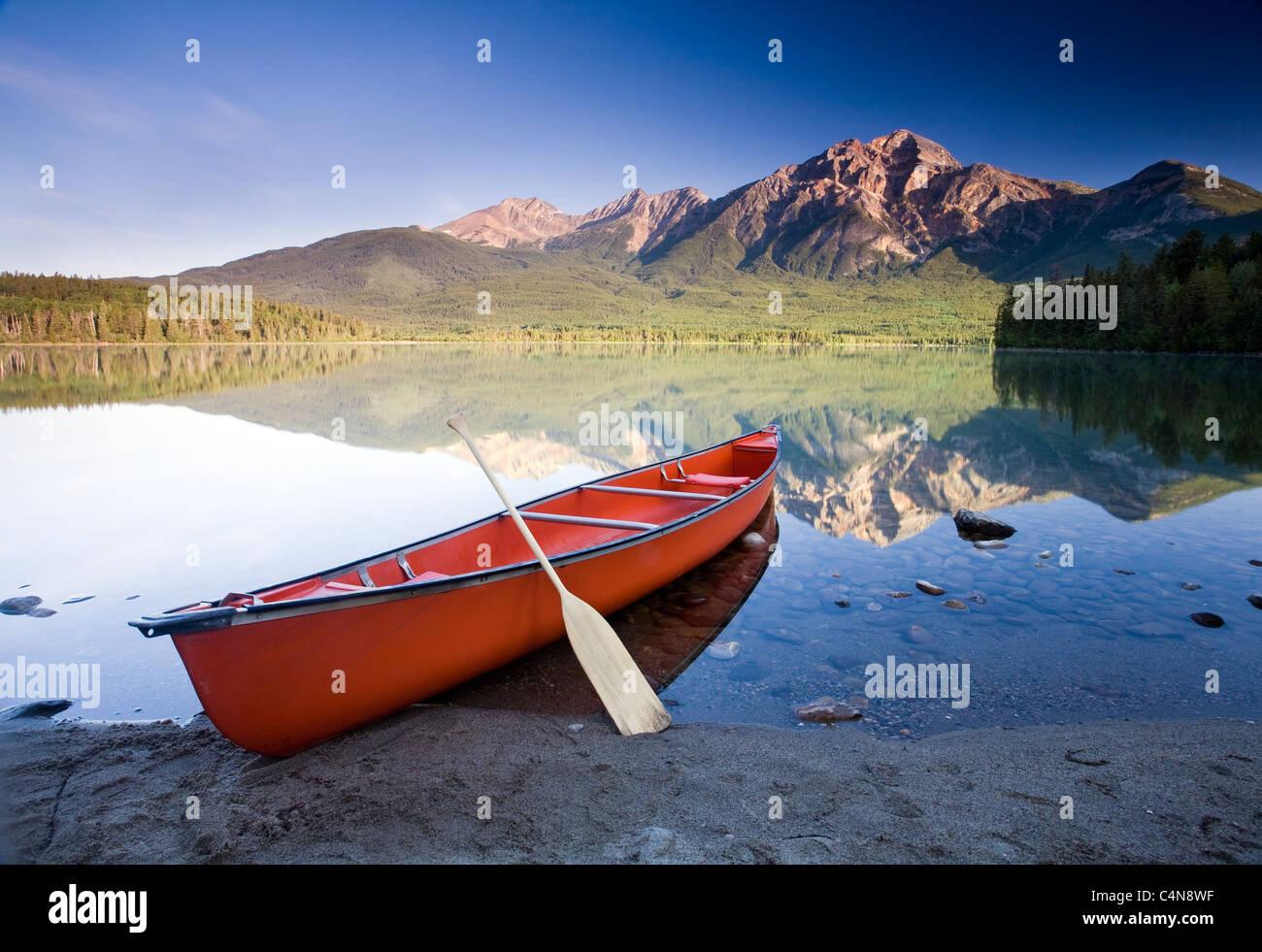 Red Canoe à l'aube sur le lac Pyramid, Jasper National Park, Alberta, Canada. Photo Stock