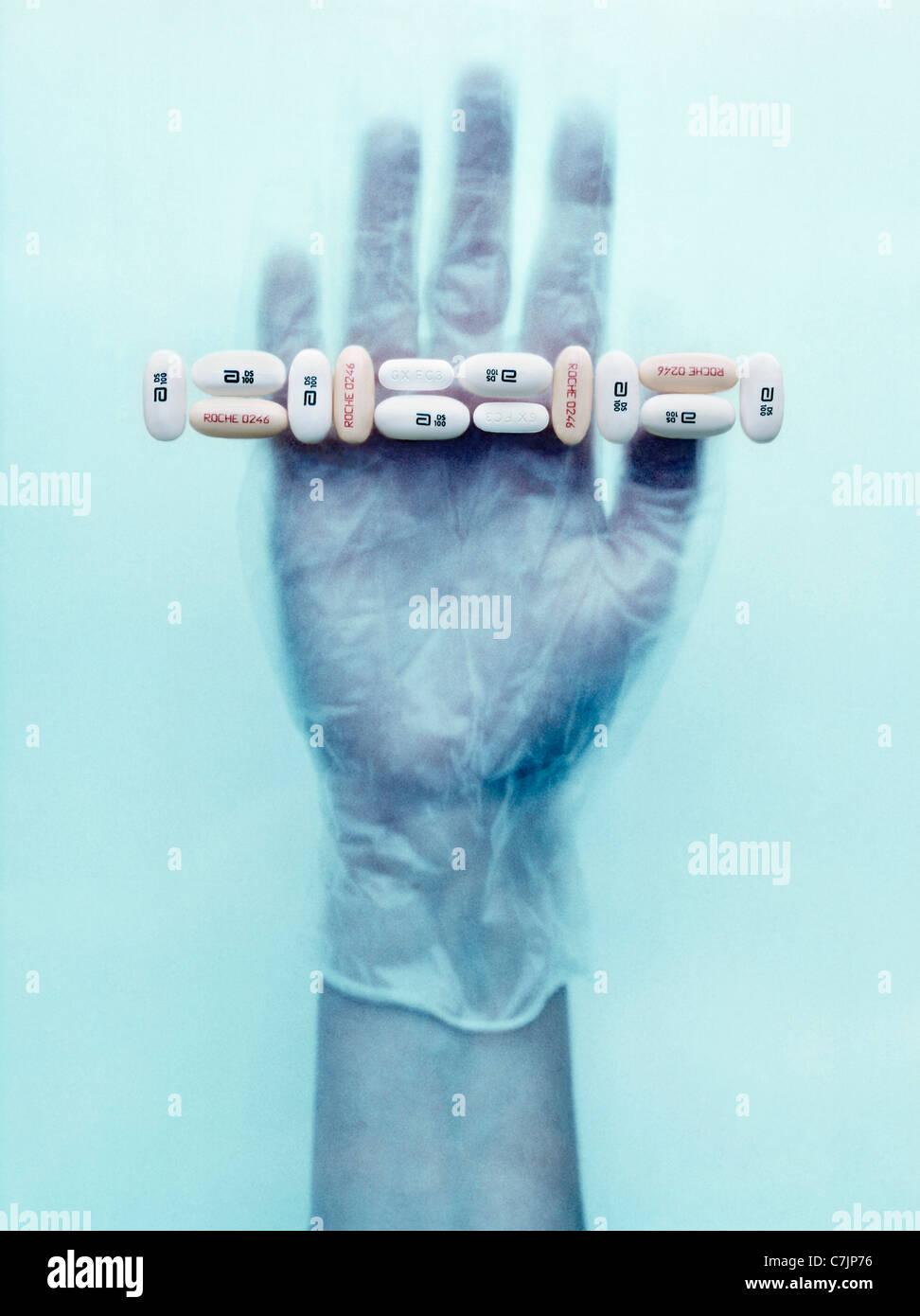 Gloved hand holding pills Photo Stock