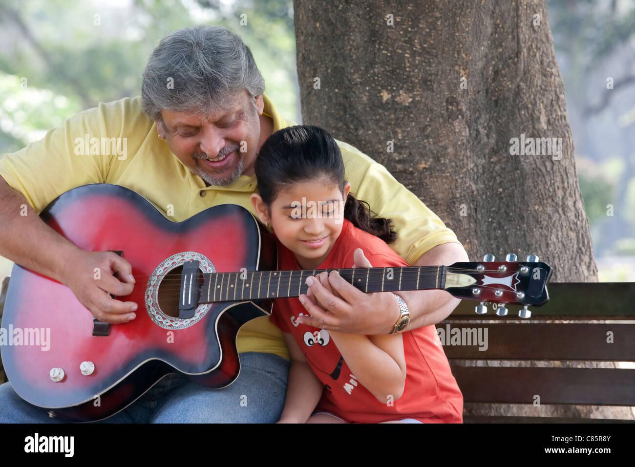 L'enseignement de son grand-père sa petite-fille à jouer de la guitare Photo Stock