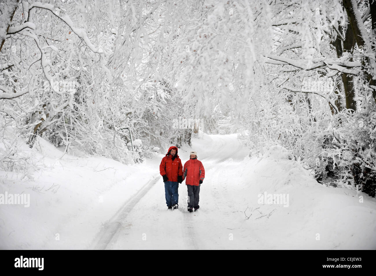 Un couple de manteaux d'hiver rouge correspondant à marcher en voie de Cotswold par temps neigeux UK Photo Stock