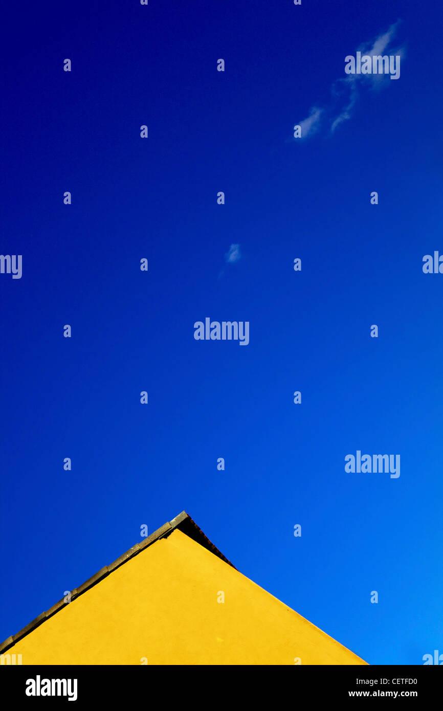 Le sommet d'un bâtiment jaune contre un ciel bleu à Beverley. Photo Stock