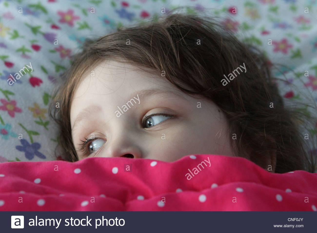 Un petit enfant au lit avec des couvertures sont arrêtés dans les yeux. Photo Stock