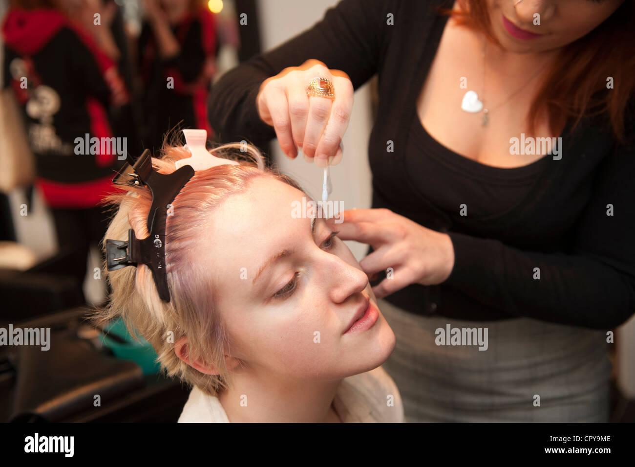 Une jeune femme ayant un cheveux et maquillage beauté make-over dans un salon, blanchiment ses sourcils, UK Photo Stock