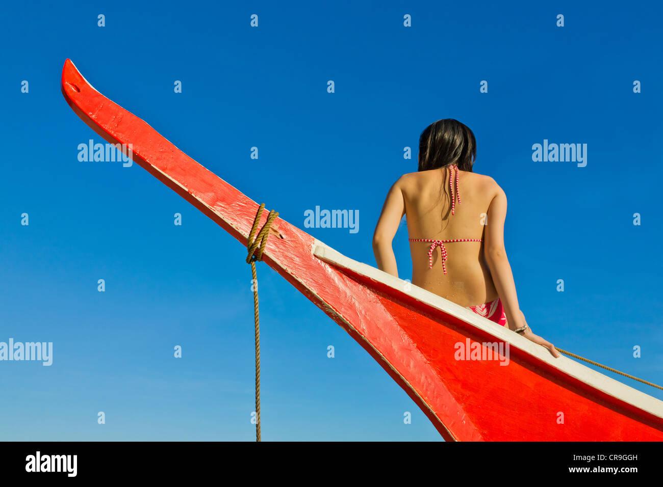 Femme assise sur bateau peint rouge, île de Bohol, Philippines Photo Stock