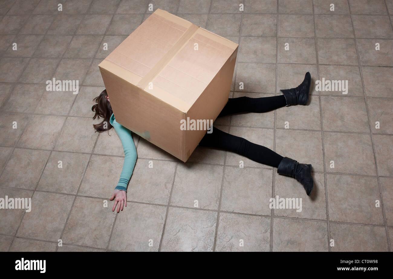Teenage girl lying sous boîte carton Photo Stock