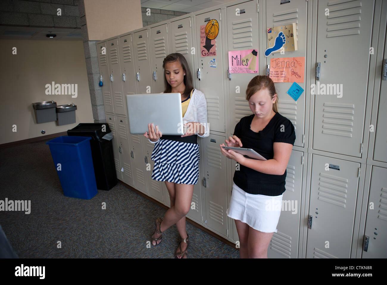 Les jeunes filles à l'aide d'ipad et d'un ordinateur portatif dans le couloir de l'école Photo Stock